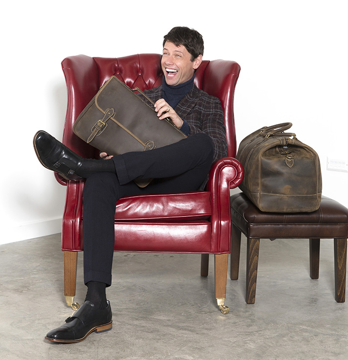 Leon Ockenden models Tusting leather briefcase and holdall whilst sitting in a Tusting leather Berkly highback chair