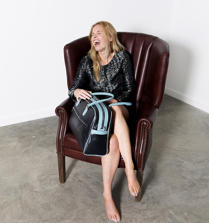Ester Coren Models a Tusting Charlotte Leather Handbag and sits in a Tusting Leather Highback Chair
