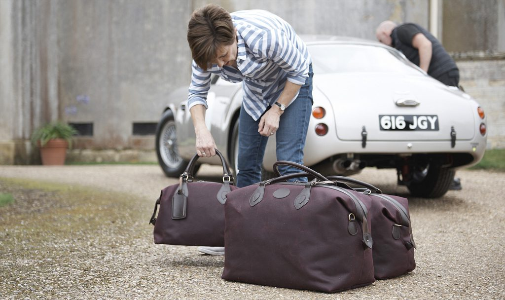 Arranging the bags and car at the photoshoot where a 1961 Aston Martin DB4 GT Zagato helped the Tusting Luggage look right at home.