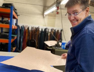 Helping the NHS | Alistair Tusting creating patterns and cutting out surgical scrubs in his leather goods factory